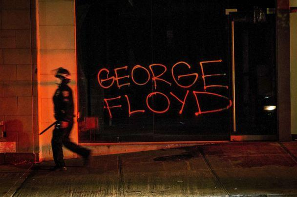 PHOTO: A New York Police Department (NYPD) officer wields a baton as he walks by a graffiti reading the name 'George Floyd' during a protest in New York City, May 31, 2020, during protests. (Alba Vigaray/EPA via Shutterstock)
