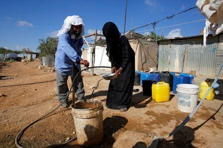 A Palestinian man washes a dish for a woman near their houses on the outskirts of the West Bank village of Yatta, south of Hebron, August 17, 2016. REUTERS/Mussa Qawasma
