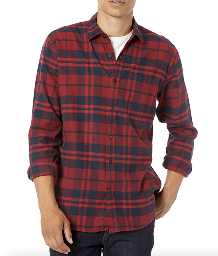 man posing with red and navy flannel shirt with hand in pocket