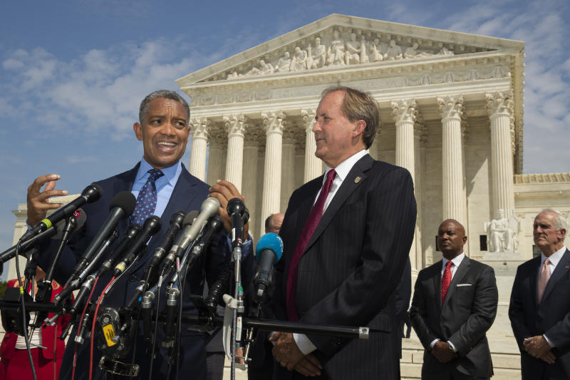 District of Columbia Attorney General Karl Racine, with Texas Attorney General Ken Paxton, right, and a bipartisan group of state attorneys general speaks to reporters in front of the U.S. Supreme Court in Washington, Monday, Sept. 9, 2019 on an antitrust investigation of big tech companies. (AP Photo/Manuel Balce Ceneta)