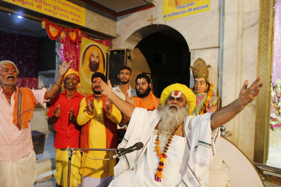 Hindu holy man Shri Narsingh Das Maharaja, right, celebrates after a verdict in a decades-old land title dispute between Muslims and Hindus, in Ayodhya, India, Saturday, Nov. 9, 2019. India's Supreme Court on Saturday ruled in favor of a Hindu temple on a disputed religious ground and ordered that alternative land be given to Muslims to build a mosque. The dispute over land ownership has been one of the country's most contentious issues. (AP Photo/Rajesh Kumar Singh)