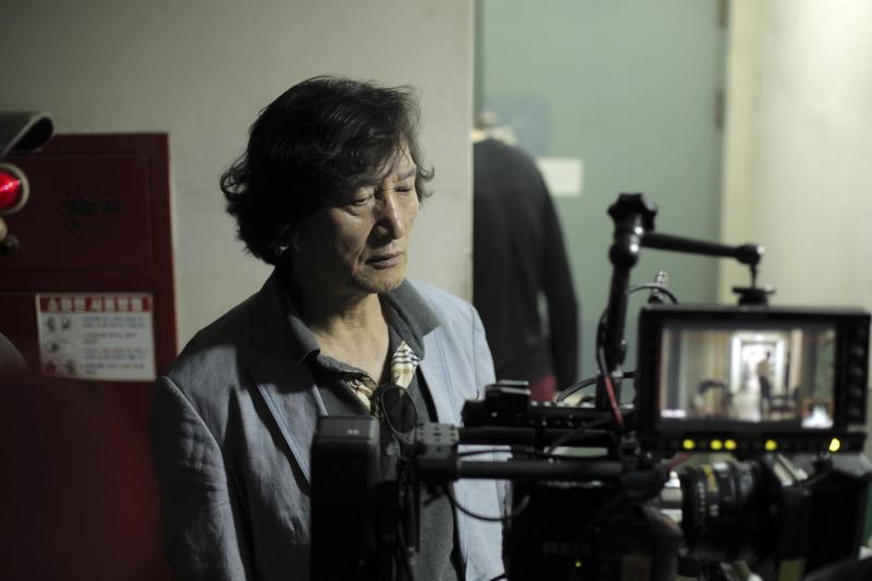 """In this undated photo released on Friday, Oct. 5, 2012 by Busan International Film Festival, South Korean director Chung Ji-young looks at a monitor for his movie """"National Security"""" in South Korea. The film based on the memoir of a democracy activist who was tortured in the 1980s by South Korea's military rulers is provoking discussion about the country's not-so-distant authoritative past and the influence it will have on this year's presidential election. (AP Photo/Busan International Film Festival) EDITORIAL USE ONLY"""