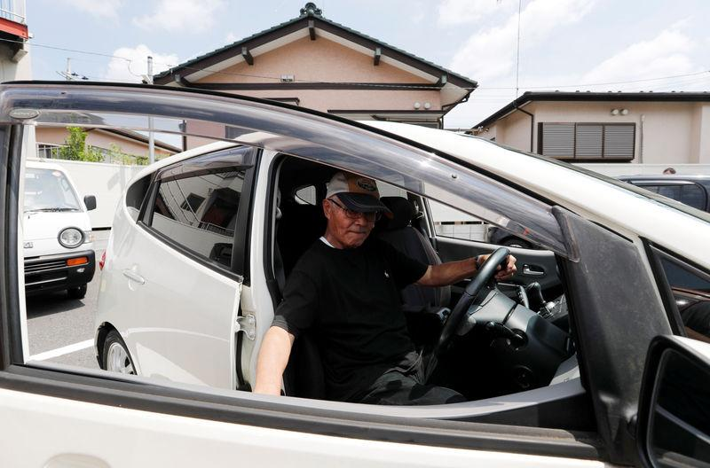 Yorie Miho drives his minicar after visiting a minicar dealership in Yamato