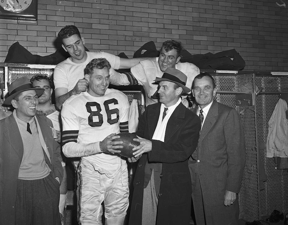 Dub Jones is given the game ball after he accounted for all the Browns TDs in their 42-21 romp over the Bears in 1951. Left to right (front): Jones; Paul Brown and Blanton Collier, backfield coach. Rear: QB Otto Graham and Capt. Tony Adamle. (Associated Press)