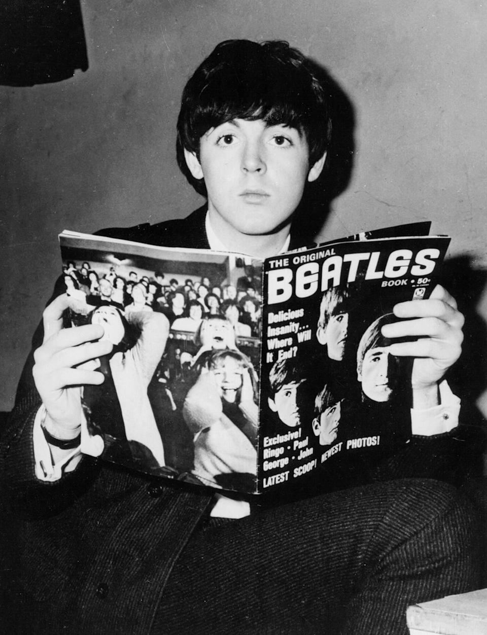 <p>Holding a Beatles fan magazine in 1964. </p>