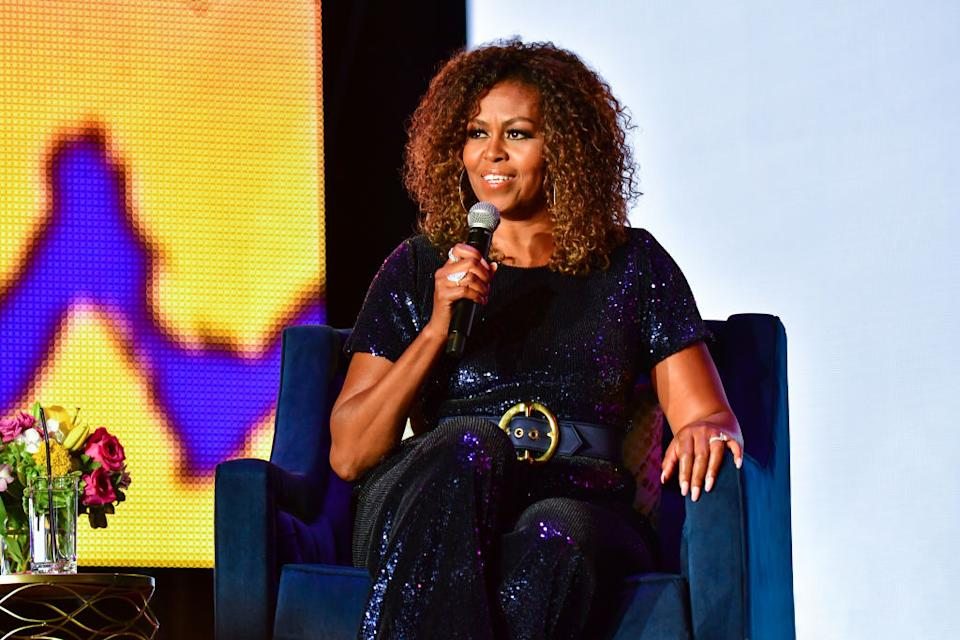 Michelle Obama has regularly showed off her natural curls, pictured at the ESSENCE Festival in 2019. (Photo by Erika Goldring/Getty Images)