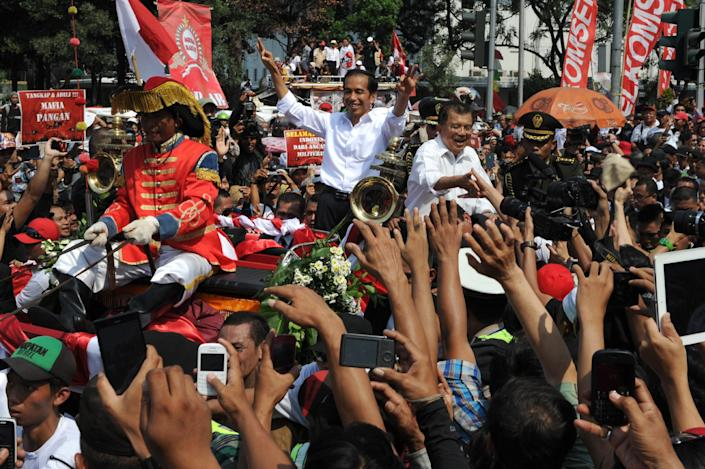 Indonesian President Joko Widodo (centre) rides on a horse-drawn carriage as they greet the crowd as their motorcade makes its way towards the presidential palace in Jakarta, on October 20, 2014 (AFP Photo/Romeo Gacad)