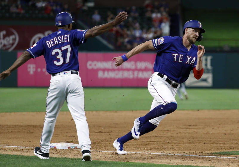 Texas Rangers third base coach Tony Beasley (37) waves Hunter Pence (24) home as Pence scores on a Nomar Mazara double during the sixth inning of a baseball game against the Seattle Mariners in Arlington, Texas, Tuesday, May 21, 2019. (AP Photo/Tony Gutierrez)