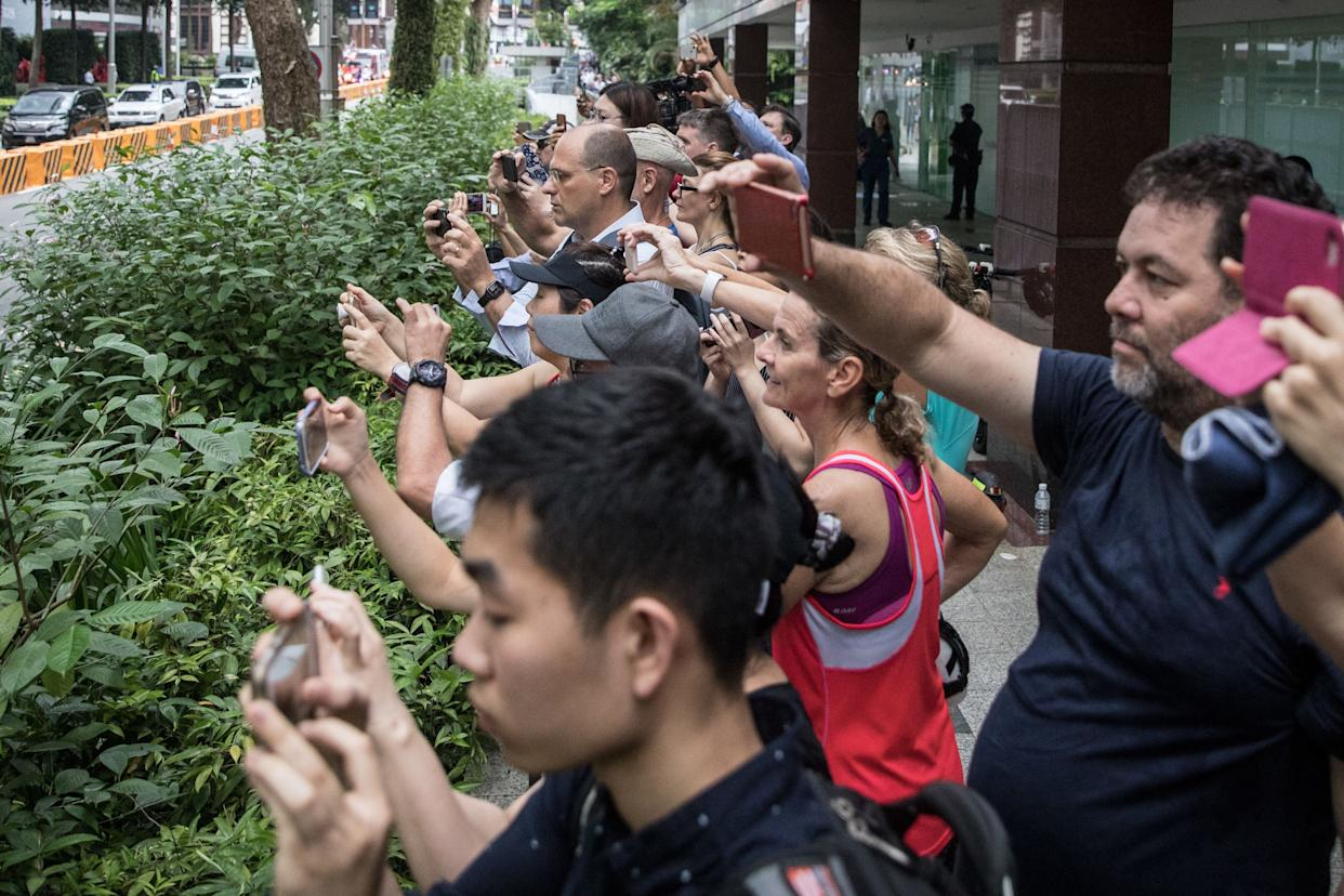 More people take photos outside the St. Regis hotel.