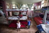 In this Nov. 13, 2013 photo, children stay in their room in the U.S.-based Church of Bible Understanding orphanage in Kenscoff, Haiti. The orphanage is run by a Christian missionary group funded by the Olde Good Things antique store on Manhattan's Upper West Side. While many other orphanages also have failed the Caribbean country's new national standards, and conditions are far worse in some, the group's three-story building on the hilly outskirts of Port-au-Prince stands out because it's run by an organization with such an unusual, and successful fundraising operation. The failure to meet the standards would seem to contradict their financial position.(AP Photo/Dieu Nalio Chery)