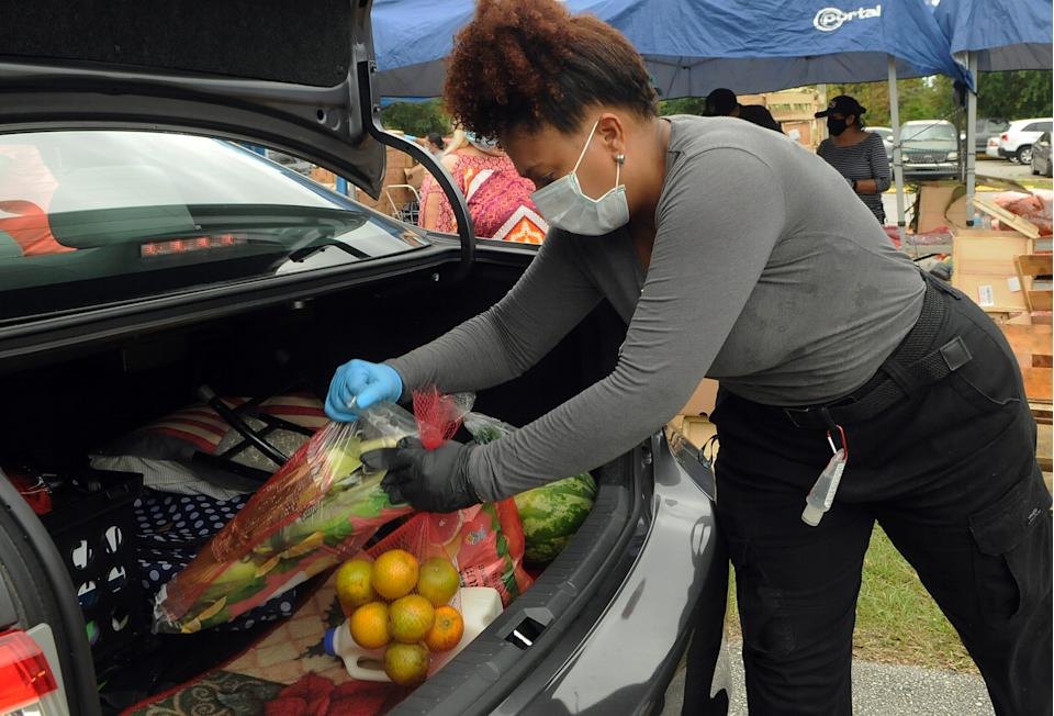 A volunteer places ears of corn and a bag of oranges from the Second Harvest Food Bank of Central Florida into the trunk of a car at a drive through food distribution event for needy families on April 17, 2020 at the New Jerusalem Church in Kissimmee, Florida. Food banks across the United States are experiencing a surge in demand as unemployment numbers increase due to layoffs caused by the coronavirus (COVID-19) pandemic.  (Photo by Paul Hennessy/NurPhoto via Getty Images)