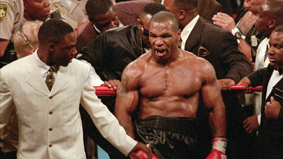 Mandatory Credit: Photo by Lennox Mclendon/AP/Shutterstock (6516209a)TYSON Mike Tyson, center, reacts to the crowd as he leaves the ring following his bout with WBA heavyweight champion Evander Holyfield, Saturday night, at the MGM Grand Garden in Las Vegas.