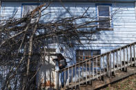 Larrecsa Cox, who leads the Quick Response Team which visits everyone who overdoses to offer help, knocks on the door of a home that suffered tree damage from a recent storm as she checks on a client in Huntington, W.Va., Friday, March 19, 2021. The pandemic proved the perfect storm for those already in the shadows: it drove them further into isolation, economic fragility and fear while at the same time upending the treatment and support systems that might save them. (AP Photo/David Goldman)