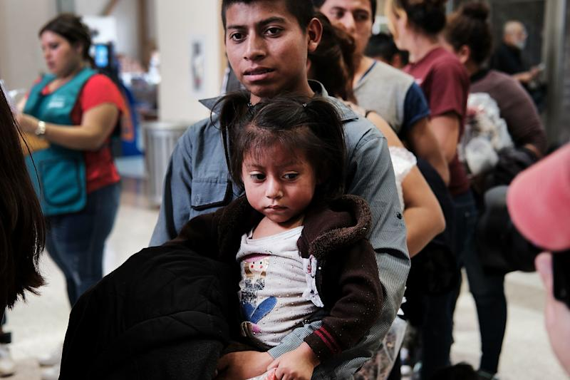 Women, men and children, many fleeing poverty and violence in Honduras, Guatemala and El Salvador, arrive at a bus station following release from Customs and Border Protection on June 23 in McAllen, Texas.
