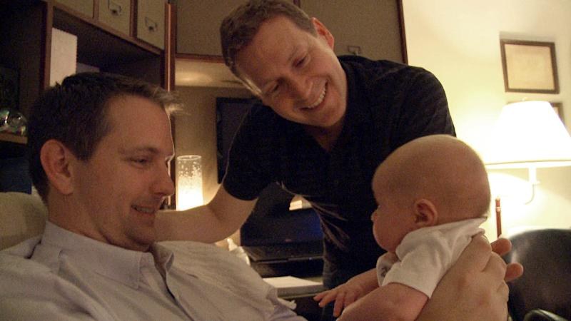 """This undated image from video released by Logo shows adoptive gay parents Mark Krieger, left, and Paul Siebold in a scene with their baby girl from """"The Baby Wait."""" """"The Baby Wait"""" is a six-part documentary series on the Logo channel that focuses equal attention on agonizing post-birth waiting periods from the perspectives of both biological and adoptive parents. (AP Photo/Logo)"""