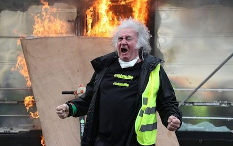A Yellow Vest protester gestures in front of a newsagent set alight during clashes with riot police - Credit: ZAKARIA ABDELKAFI/AFP