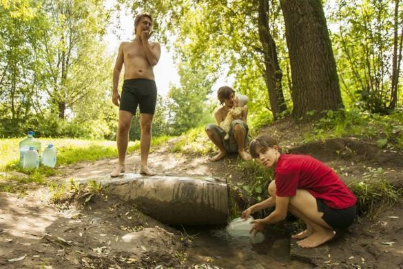Political activists Oleg Vorotnikov (L) Pyotr Verzilov (C) and his wife Nadezhda Tolokonnikova fetch water during the summer while living together in a car shed in Moscow, July 15, 2008. Tolokonnikova later became a member of Pussy Riot.