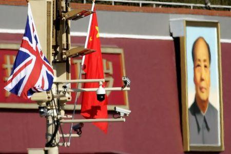 A Union flag and a Chinese flag are placed at a pole with security cameras in front of a portrait of late Chinese Chairman Mao Zedong at the Tiananmen gate during a visit by British Prime Minister Theresa May to China, in Beijing, January 31, 2018. REUTERS/Jason Lee/Files