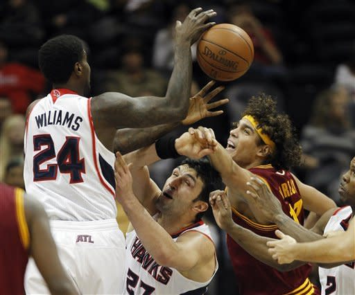 Atlanta Hawks' Marvin Williams (24) and Zaza Pachulia (27) battle Cleveland Cavaliers power forward Anderson Varejao (17) for a rebound in the first half of an NBA basketball game on Saturday, Jan. 21, 2012, in Atlanta. (AP Photo/John Bazemore)