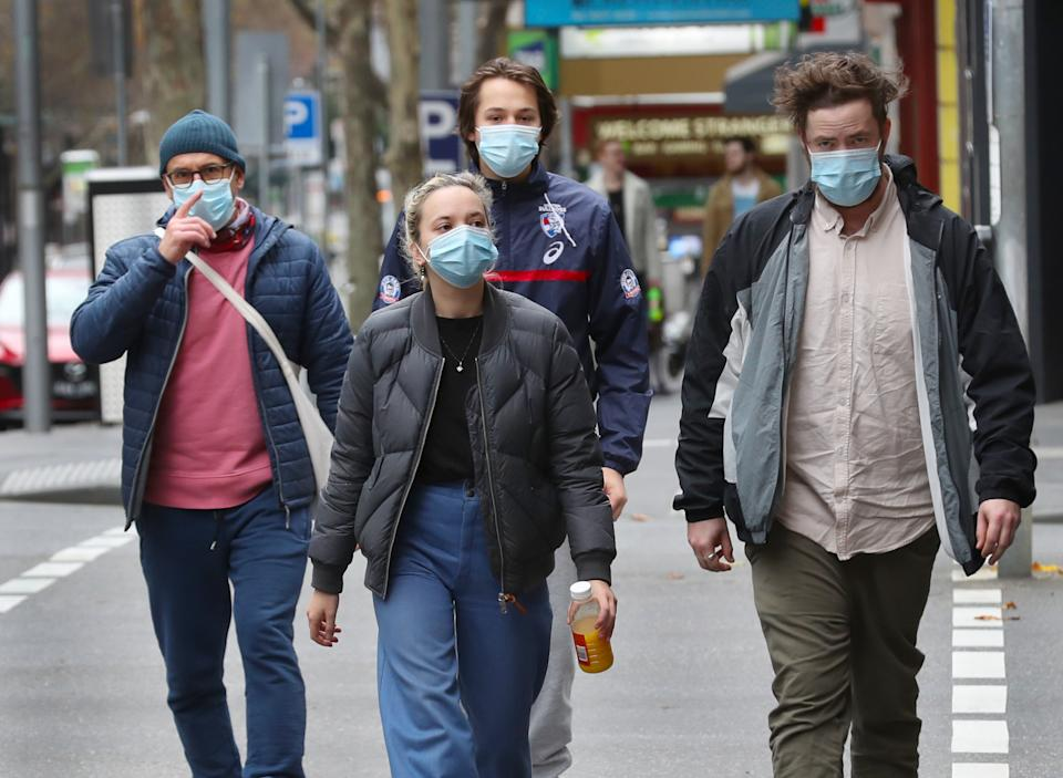 People are seen wearing masks in Bourke street in Melbourne.