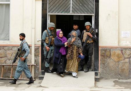 Women react as they walk past Afghan soldiers outside a hospital after multiple explosions in Kabul, Afghanistan, March 21, 2019. REUTERS/Parwiz