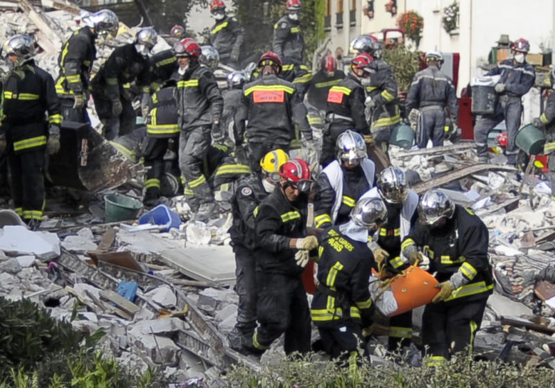 Firefighters carry a body found in the rubble of a four-storey residential building that collapsed following a blast in Rosny-sous-Bois in the eastern suburbs of Paris on August 31, 2014 (AFP Photo/Fred Dufour)