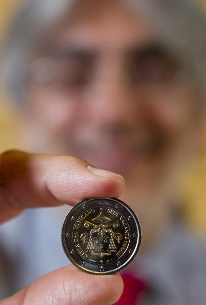 In this picture taken on Tuesday, June 4, 2013, Mauro Olivieri, head of the Vatican Philatelic and Numismatic Office, shows a two-Euro coin mint for the 2013 Vacant See during an interview with the Associated Press in his office at the Vatican. The Vatican still hasn't fully solved an embarrassing shutdown in credit card services, despite announcing four months ago that systems were back up - as Pope Benedict XVI's shock resignation laid the ground for a bonanza in Vatican-minted papal memorabilia. The impact has been far worse than the Vatican ever let on, costing the Holy See a fortune at a time when the Catholic world is still buzzing with excitement about the election of Pope Francis. (AP Photo/Domenico Stinellis)