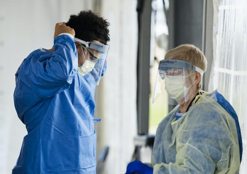 Two health-care professionals, one of whom is adjusting a face shield and the other is putting on a yellow protective gown.