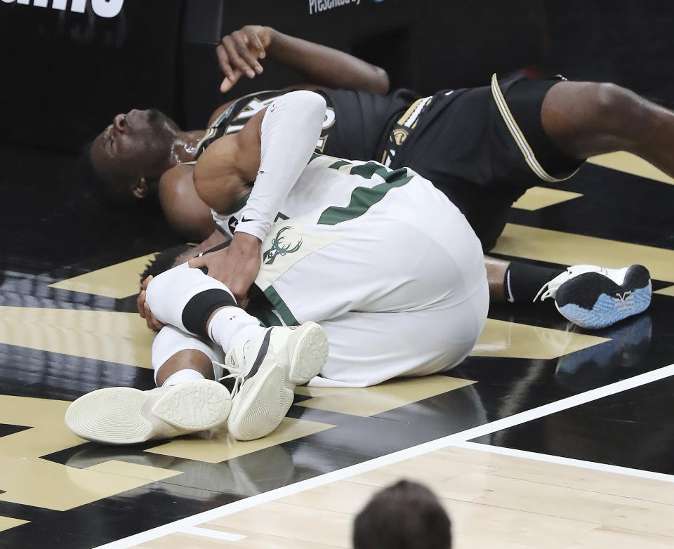 Milwaukee Bucks forward Giannis Antetokounmpo hyperextends his left knee on this play hitting the floor after rising to challenge a slam by Atlanta Hawks center Clint Capela on a lob pass by Lou Williams with 7:14 left in the third quarter of game 4 in the NBA Eastern Conference Finals on Tuesday, June 29, 2021, in Atlanta. (Curtis Compton/Atlanta Journal-Constitution via AP)