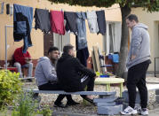 """Syria refugee sits in a garden at a refugee center in Bialystok, Poland, on Wednesday, Sept. 29, 2021. After enduring a decade of war in Syria, Boshra al-Moallem and her two sisters seized their chance to flee, but the journey proved terrifying and nearly deadly. Al-Moallem, originally from Homs but who displaced to Damascus by the war, is one of thousands of people who have traveled to Belarus in recent weeks and then found herself helped to cross the border with the help of Belarusian guards, something the EU considers a form of """"hybrid war"""" waged against the bloc with the use of human lives. (AP Photo/Czarek Sokolowski)"""