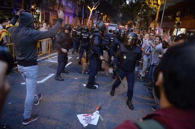 <p>Pro-referendum demonstrators protest as Spanish National Police officers leave during a demonstration near the Economy headquarters of Catalonia's regional government in Barcelona on Sept. 20, 2017. (Photo: Lluis Gene/AFP/Getty Images) </p>