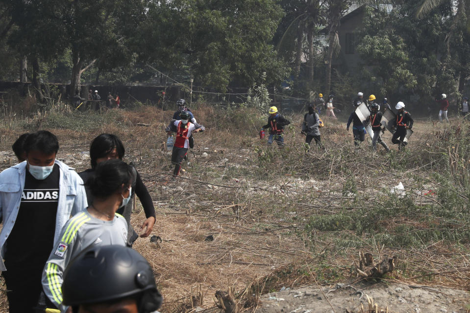 Anti-coup protesters run in an open field after police security forces try to disperse them with tear gas in Mandalay, Myanmar Saturday, March 13, 2021. Police in Myanmar fired rubber bullets and tear gas at protesters in the country's two largest cities and elsewhere on Friday, as authorities continued their harsh crackdown on opponents of last month's military coup. (AP Photo)