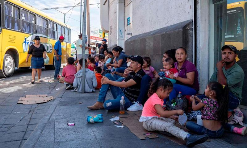Migrants, mostly from Mexico, are pictured sitting on the ground waiting near the Paso del Norte Bridge at the Mexico-US border, in Ciudad Juarez, Mexico, on 12 September.