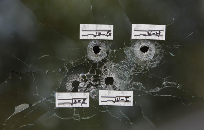 Bullet holes are seen in the front window, Monday, May 20, 2013, of the home, where Elvira Campos, 10, was shot and killed in North Highlands, Calif. Campos had been watching television with her parents Saturday night, when at least two gunmen walked up to the door of the home and began shooting. About a dozen shot were fired, killing Campos' and wounding her father and mother. (AP Photo/Rich Pedroncelli)