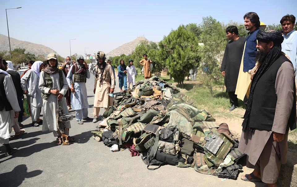 Taliban fighters stand beside the belongings of Afghan security soldiers in Kabul, the capital of Afghanistan, Aug. 16, 2021. (Str/Xinhua via ZUMA Press)