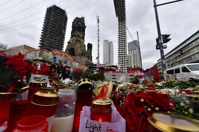 Candles, flowers and individual messages are placed at a makeshift memorial for the victims of the Christmas market attack near the Kaiser Wilhelm Memorial Church in Berlin on December 24, 2016 (AFP Photo/John MACDOUGALL)