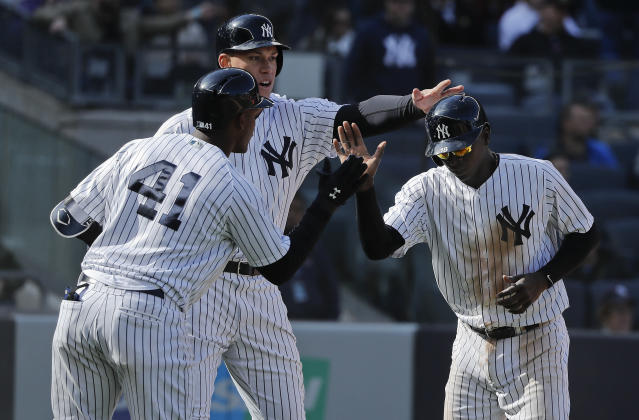 New York Yankees' Didi Gregorius, right, is greeted by Aaron Judge, center, and Miguel Andujar (41) after scoring against the Baltimore Orioles during the seventh inning of a baseball game, Saturday, April 7, 2018, in New York. (AP Photo/Julie Jacobson)