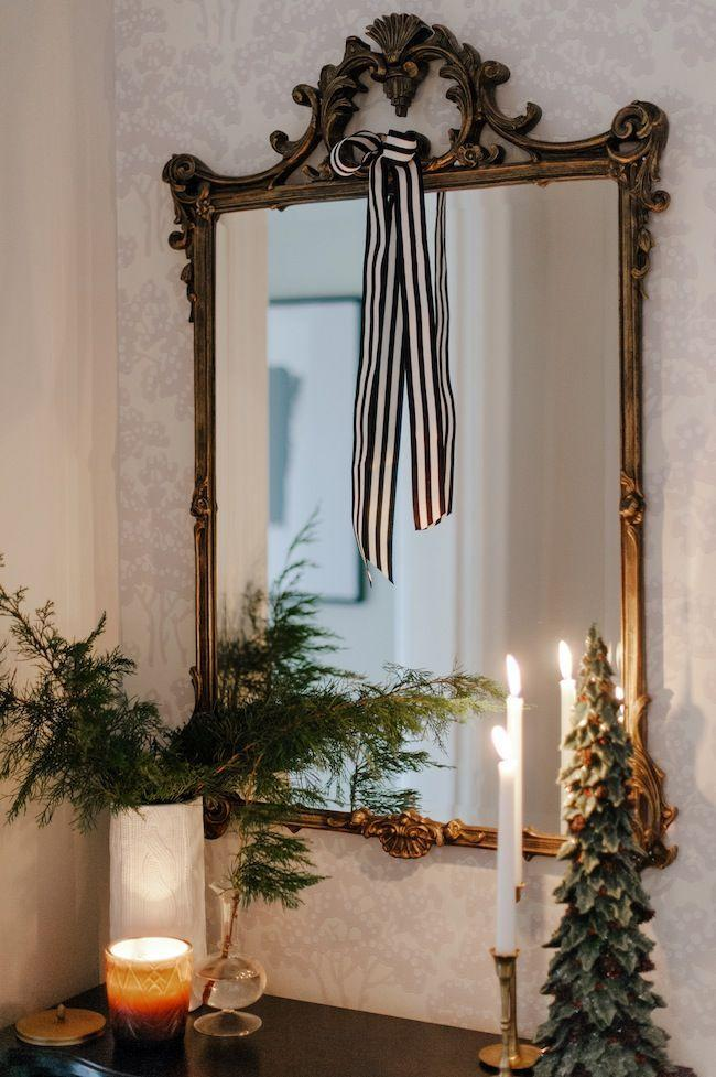 "<p>Tying a ribbon on your mirror is the stupid-easy decorating hack you never knew you needed.</p><p>See more at <a href=""http://www.jacquelynclark.com/2017/12/13/classic-christmas-home-tour/"" rel=""nofollow noopener"" target=""_blank"" data-ylk=""slk:Lark & Linen"" class=""link rapid-noclick-resp"">Lark & Linen</a>. </p>"