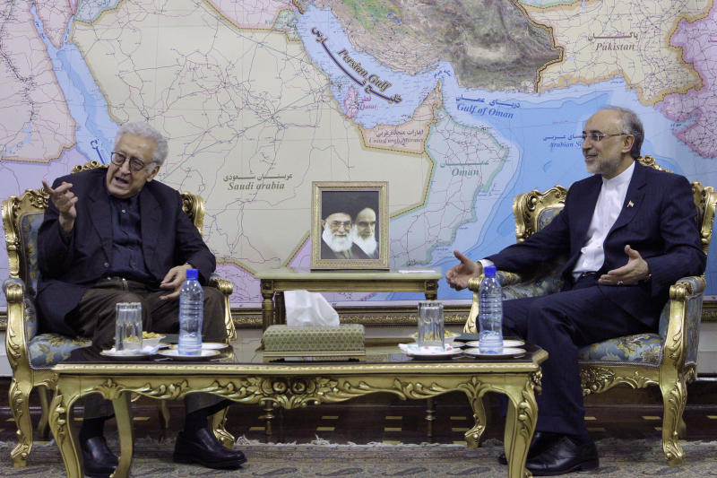 U.N. envoy on Syria, Lakhdar Brahimi, left, talks with Iranian Foreign Minister Ali Akbar Salehi, during their meeting in Tehran, Iran, Sunday, Oct. 14, 2012. Pictures of the late Iranian revolutionary founder Ayatollah Khomeini, right, and supreme leader Ayatollah Ali Khamenei, are seen at center. (AP Photo/Vahid Salemi)