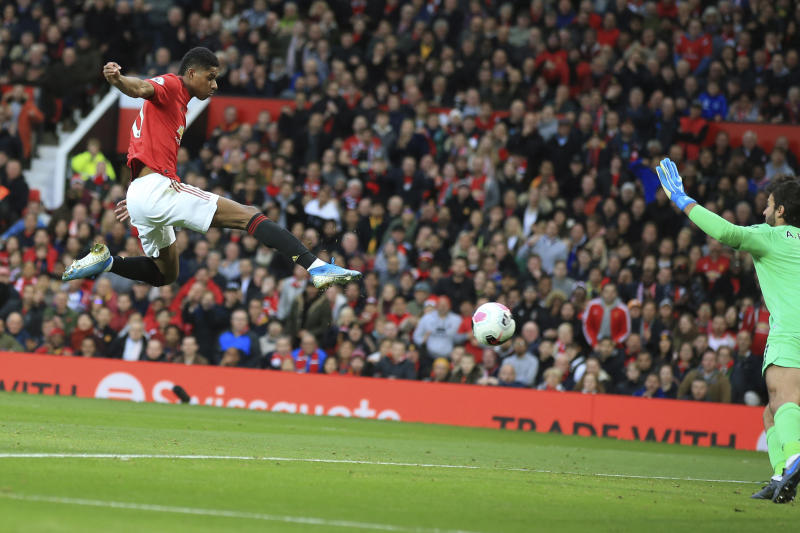 Manchester United's Marcus Rashford scores his side's opening goal during the English Premier League soccer match between Manchester United and Liverpool at the Old Trafford stadium in Manchester, England, Sunday, Oct. 20, 2019. (AP Photo/Jon Super)