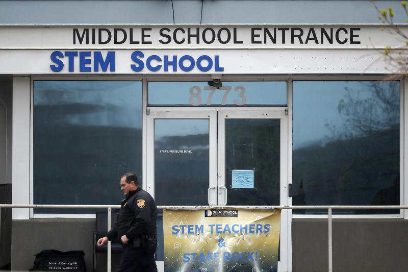 FILE - In this May 8, 2019 file photo, a Douglas County, Colo., Sheriff's deputy walks past the doors of the STEM Highlands Ranch school in Highlands Ranch, Colo. The younger of two students charged in a school shooting in suburban Denver that killed a classmate has pleaded guilty. Prosecutors say 16-year-old Alec McKinney pleaded guilty on Friday, Feb. 7, 2020 to 17 felonies, including a first-degree murder charge. In December, a judge ruled that McKinney would be prosecuted as an adult in the May 7 shooting at STEM School Highlands Ranch that killed 18-year-old Kendrick Castillo. Devon Erickson has pleaded not guilty to the same charges McKinney faced in the shooting.(AP Photo/David Zalubowski, File)