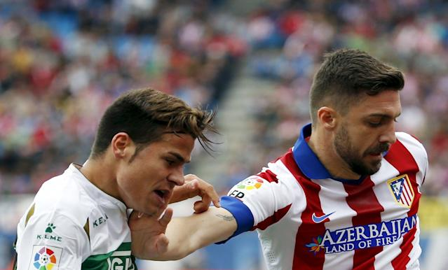 Atletico Madrid's Guilherme Siqueira (R) fights for the ball with Elche's Samuel Martinez during their Spanish first division soccer match at Vicente Calderon stadium in Madrid, April 25, 2015. REUTERS/Susana Vera