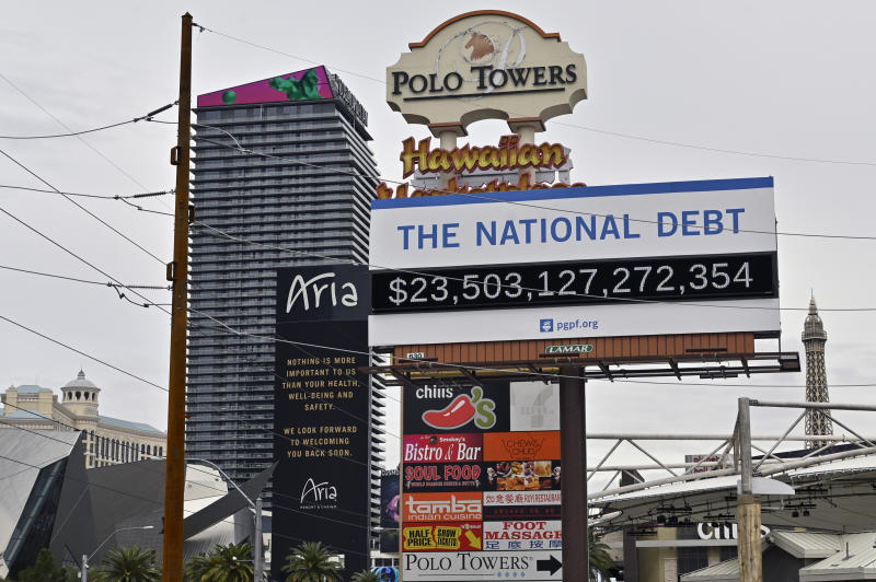 A billboard displaying the U.S. national debt is displayed along the Las Vegas Strip after all the casinos and non-essential businesses in the state were ordered to shut down due to the coronavirus Wednesday, March 18, 2020, in Las Vegas. For most people, the new coronavirus causes only mild or moderate symptoms, such as fever and cough. For some, especially older adults and people with existing health problems, it can cause more severe illness, including pneumonia. (AP Photo/David Becker)
