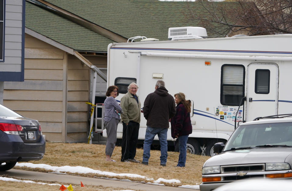 Neighbors gather on the lawn next to the home of Kirby Klements after a piece of debris crushed the man's pickup truck parked next to his home in Broomfield, Colo., as the plane shed parts while making an emergency landing at nearby Denver International Airport Saturday, Feb. 20, 2021. (AP Photo/David Zalubowski)