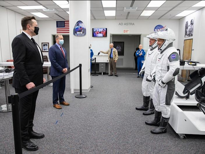 Elon Musk (left) and NASA Administrator Jim Bridenstine greet NASA astronauts Robert Behnken (left) and Douglas Hurley inside the Astronaut Crew Quarters at the Kennedy Space Center in Florida, ahead of Wednesday's launch attempt, May 27, 2020.