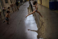 Children jump over a puddle of water as they play during a rainstorm on a street in Barcelona, Spain, Saturday, Sept. 18, 2021. (AP Photo/Emilio Morenatti)