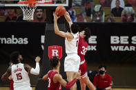 Indiana guard Trey Galloway (32) grabs the arm of Rutgers guard Geo Baker (0) as Rutgers center Myles Johnson (15) watches during the second half of an NCAA college basketball game, Wednesday, Feb. 24, 2021, in Piscataway, N.J. Rutgers defeated Indiana 74-63. (AP Photo/Kathy Willens)