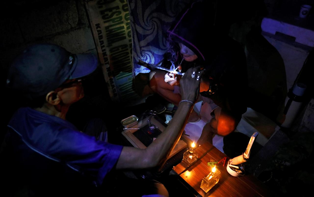 "REFILE - QUALITY REPEAT  A drug user inhales ""Shabu"", or methamphetamine, at a drug den in Manila, Philippines February 13, 2017. Picture taken February 13, 2017. To match Insight PHILIPPINES-DRUGS/      REUTERS/Erik De Castro"