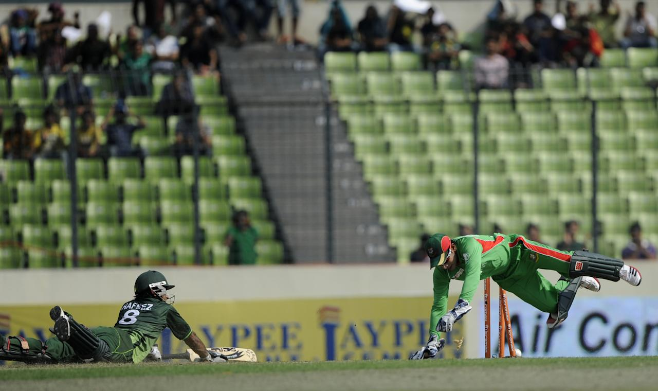 Bangladeshi cricket captain Mushfiqur Rahim (R) attempts to run out Pakistan batsman Mohammad Hafeez as he tries to make his ground during the one day international (ODI) Asia Cup cricket match between Bangladesh and Pakistan at The Sher-e-Bangla National Cricket Stadium in Dhaka on March 11, 2012.      AFP PHOTO/Munir uz ZAMAN (Photo credit should read MUNIR UZ ZAMAN/AFP/Getty Images)