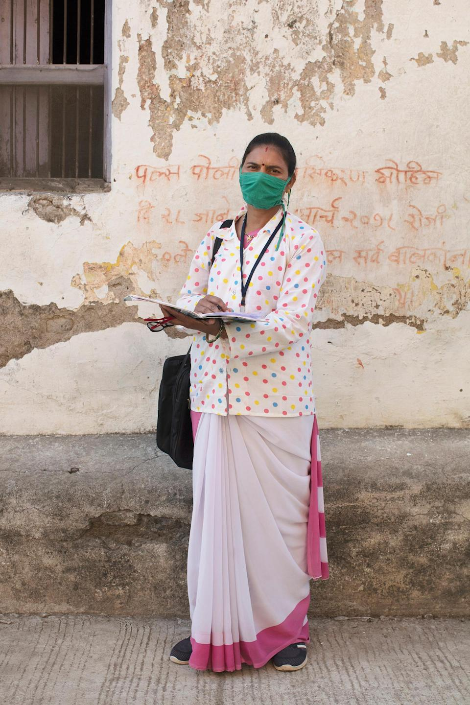 """Portrait of Archana Ghugare, a community health worker, in Pavnar, Maharashtra, India, on Dec. 1, 2020. In the background is a message encouraging people to bring their children for the Polio vaccine drive.<span class=""""copyright"""">Prarthna Singh for TIME</span>"""